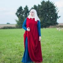 Surcot aus zweifach mit Krapp gefärbtem Wollkörper. Darunter ein blaues Kleid.