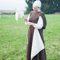 Einfaches Kleid mit Schlupfärmeln aus ungefärbter, naturbrauner Wolle. Dazu ein Haarsack.