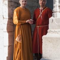 Darstellung eines bürgerlichen Paares. Das Kleid der Frau hat leichte Überlänge, der Kopfschmuck ist modisch. Der Mann trägt einen Rock aus mittelschwerem Wollkörper, der mit Krapp gefärbt wurde.