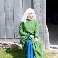 Ingoblaues Kleid mit einem weiteren Kleid, das mit Indigo und Reseda gefärbt wurde darüber. Der Gürtel ist schwarz und mit Beschlägen aus Messing versehen.