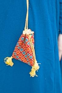 Mit Seide bestickter Reliquienbeutel. Die Seide ist pflangengefärbt und mit dem Ziegelstich auf einen Leinengrund gestickt. Die Bänder sind in Fingerloop-Technik geflochten und ebenfalls aus pflanzengefärbter Seide.