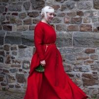 Mit Krapp gefärbtes Kleid aus feinem Wollkörper. Dazu ein Gebende mit Haarnetz.