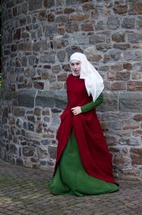 Surcot aus zweifach mit Krapp gefärbtem Wollkörper. Darunter ein grünes Kleid.